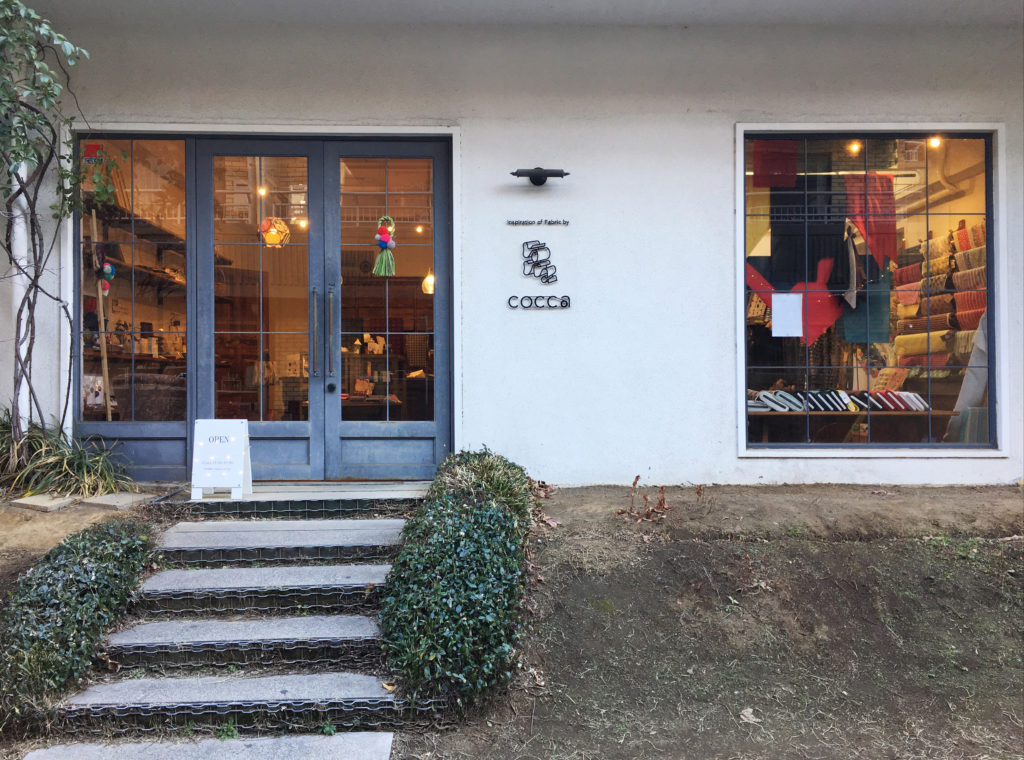 色彩のフィールドワーク:もてなす緑加藤幸枝カラフルなしめ飾り——生地屋さん店の店先にて コッカcocca