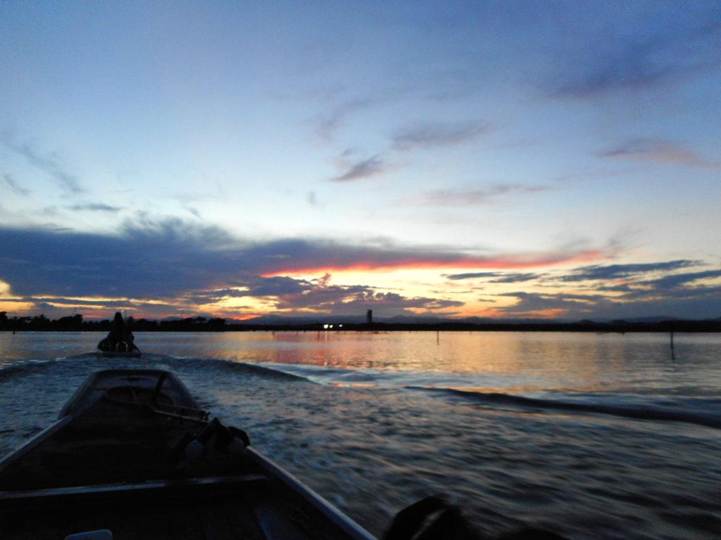 漁に出る船と夕焼けに染まる湖