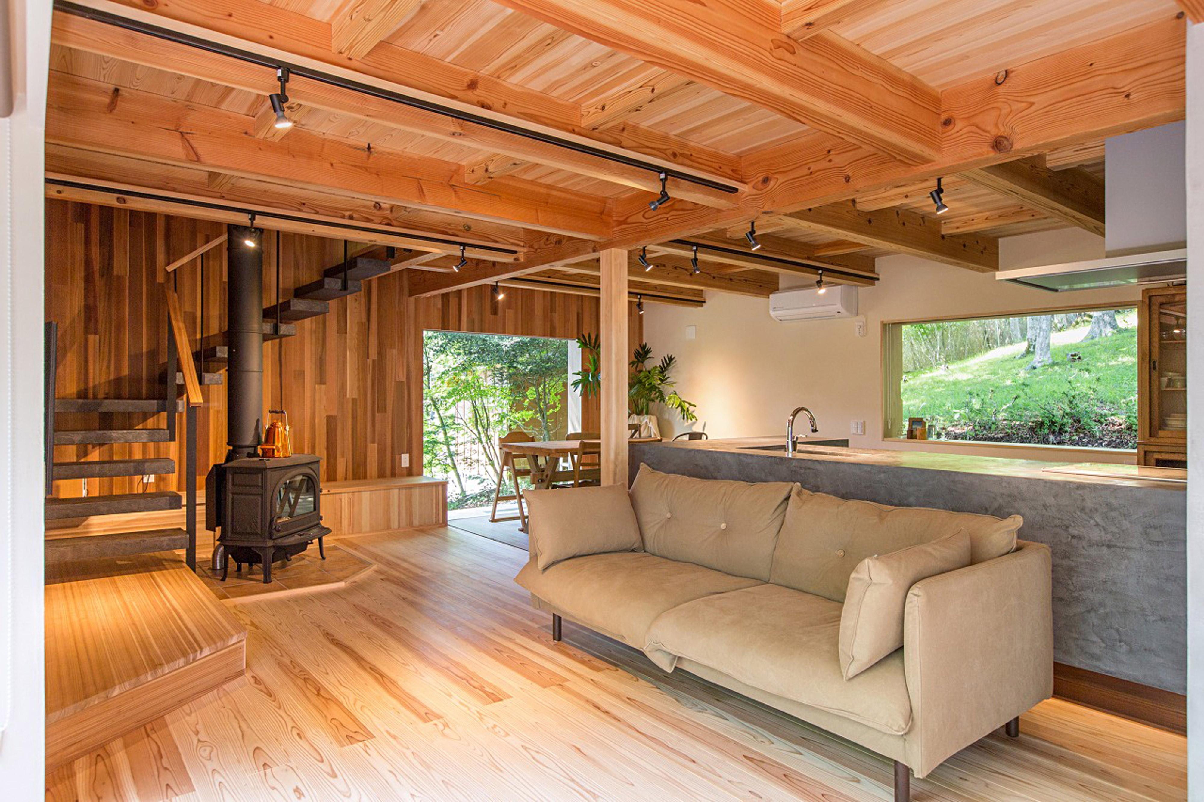 薪ストーブとソファのある全方向に窓があるリビング