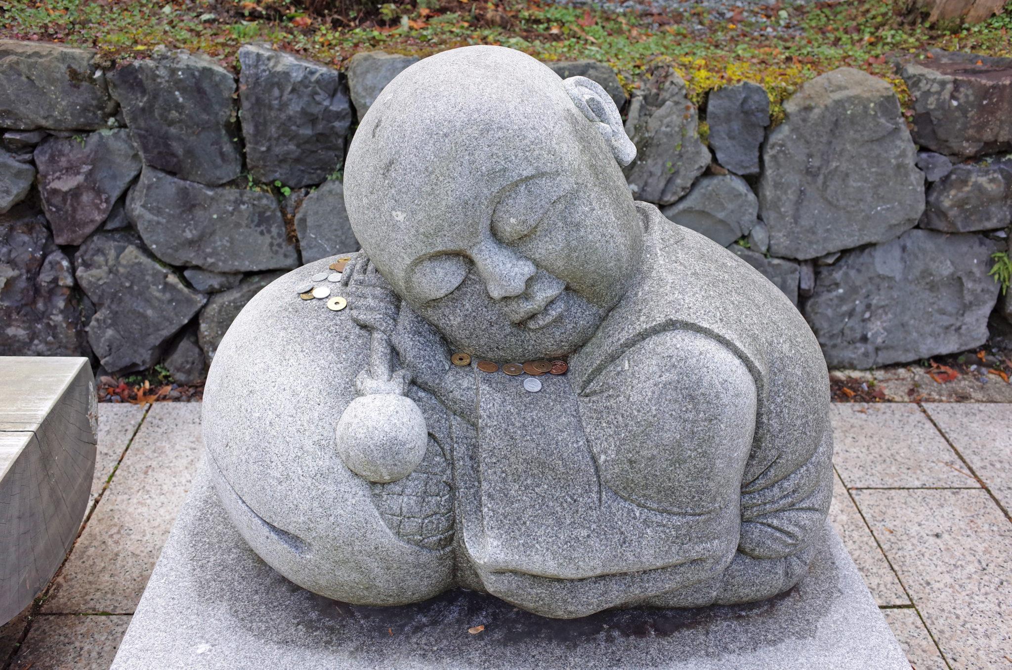 賽銭がお供えされた高野山のかわいい小坊主の石像