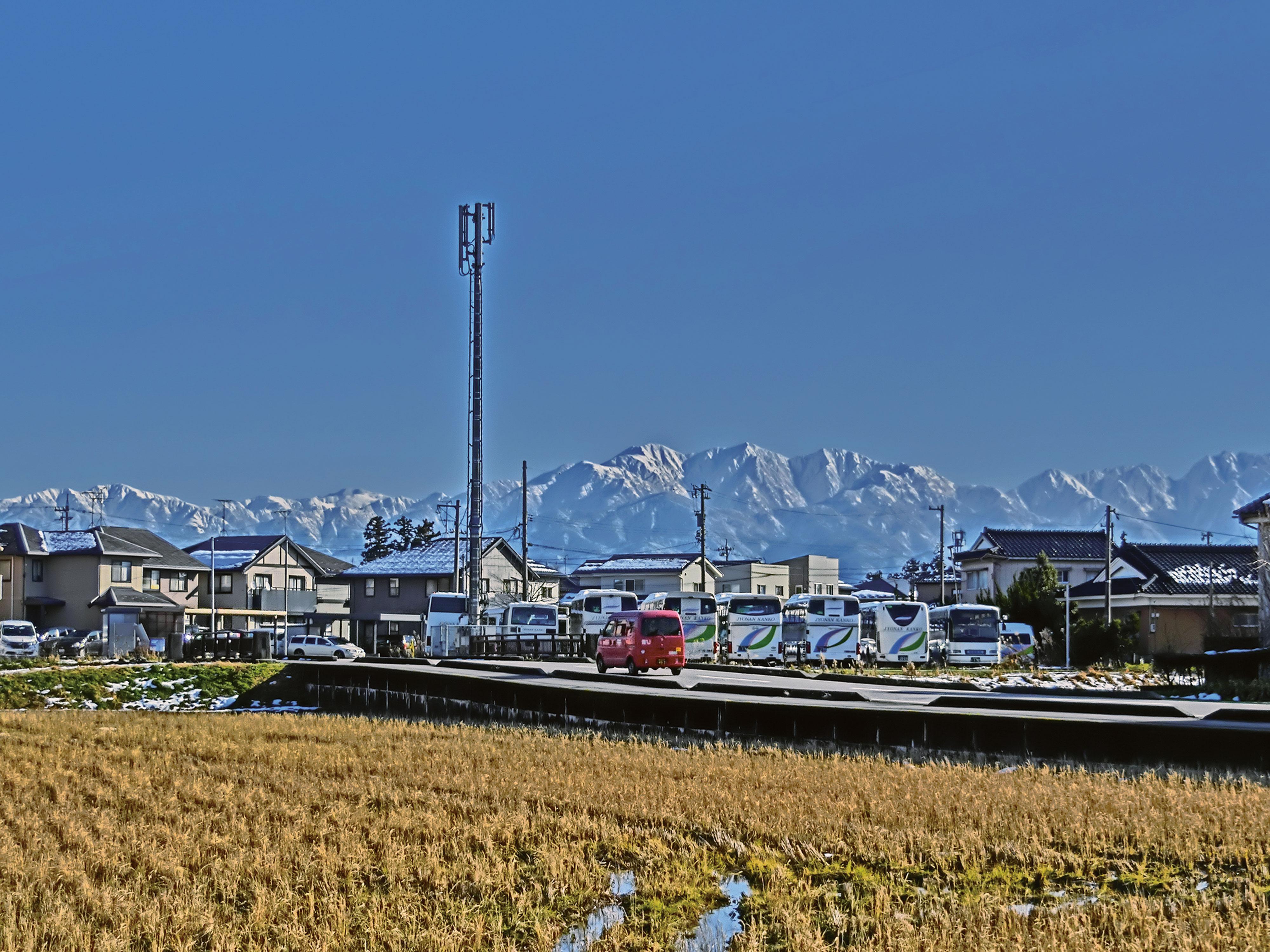 田んぼと住宅街の向こうに立山連峰