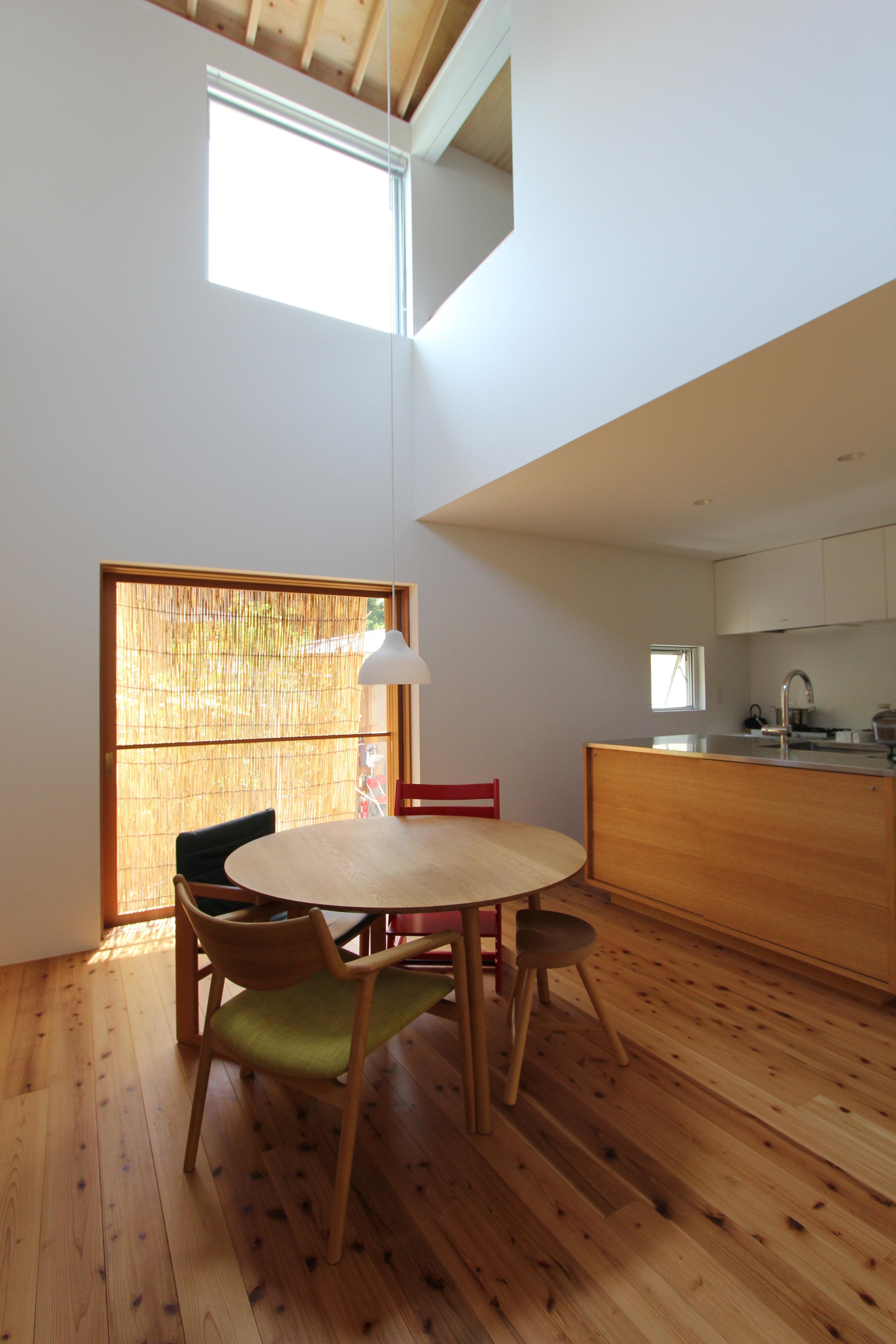 開放的な窓と吹き抜けのダイニングがあるamp/アンプ建築設計事務所イエニワハナレ