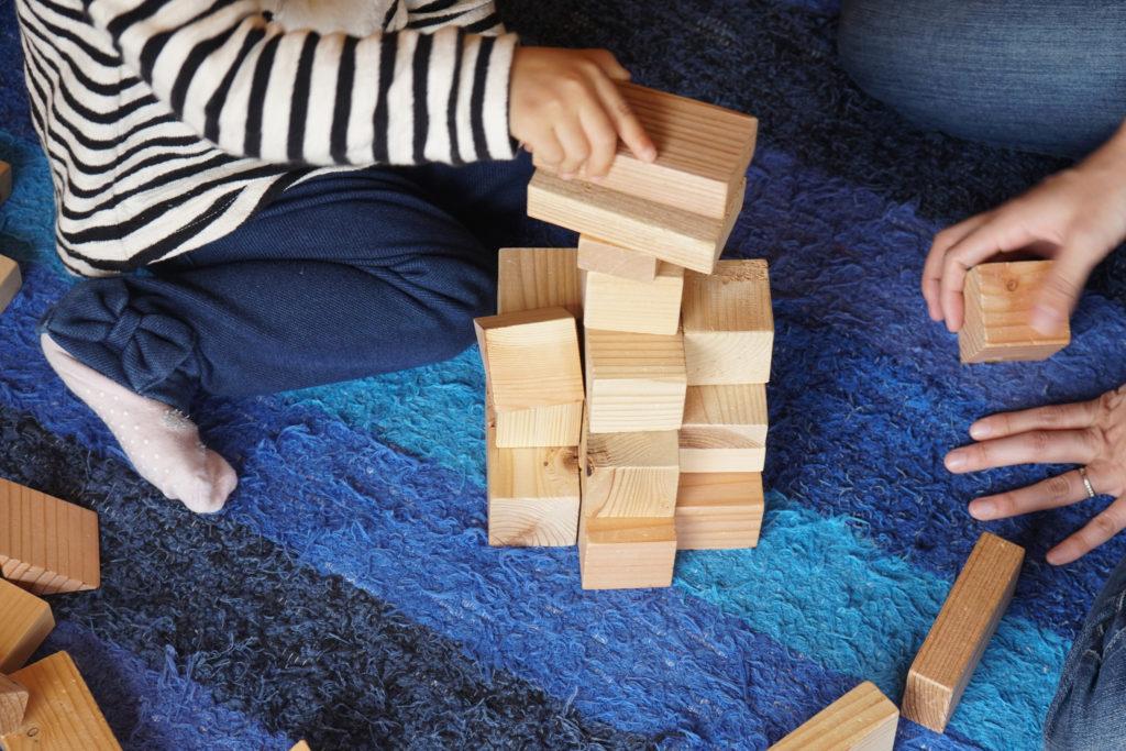 お母さんと一緒に積み木で遊ぶ子ども