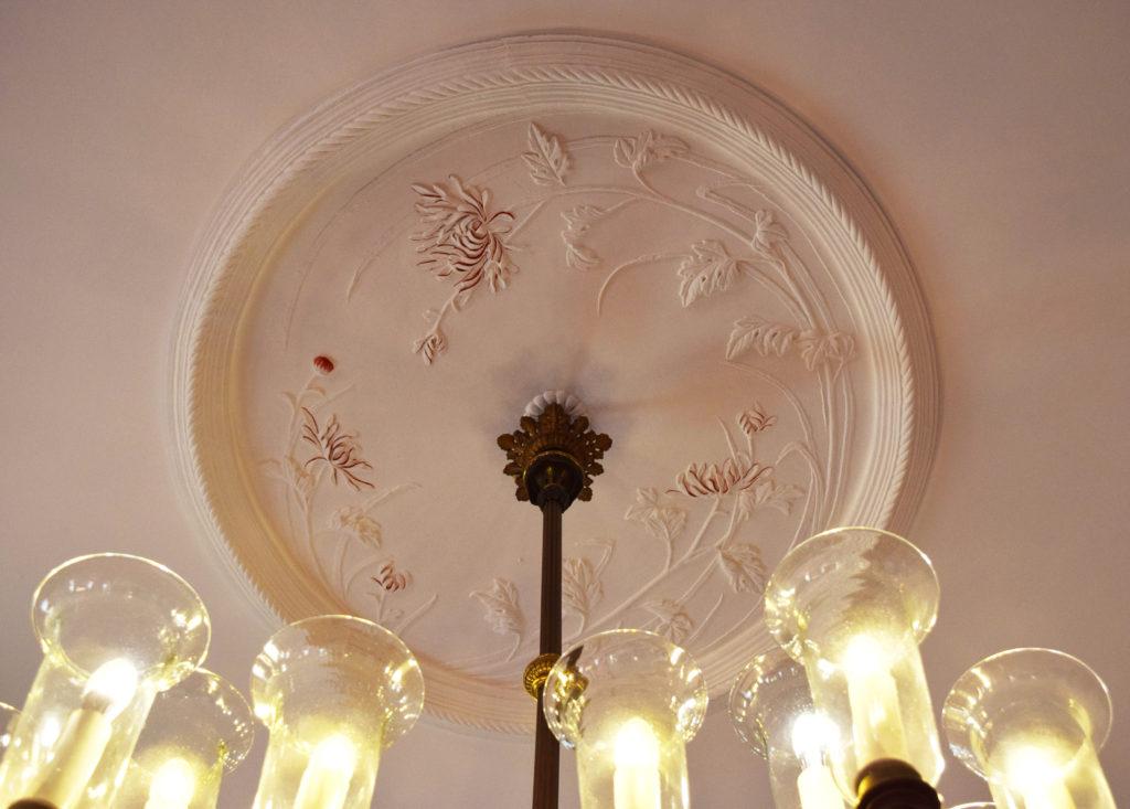 シャンデリアの接続部にある天井飾りの菊のこて絵