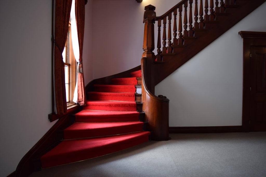 赤絨毯の階段と手すりの装飾が美しい豊平館のカーブ階段