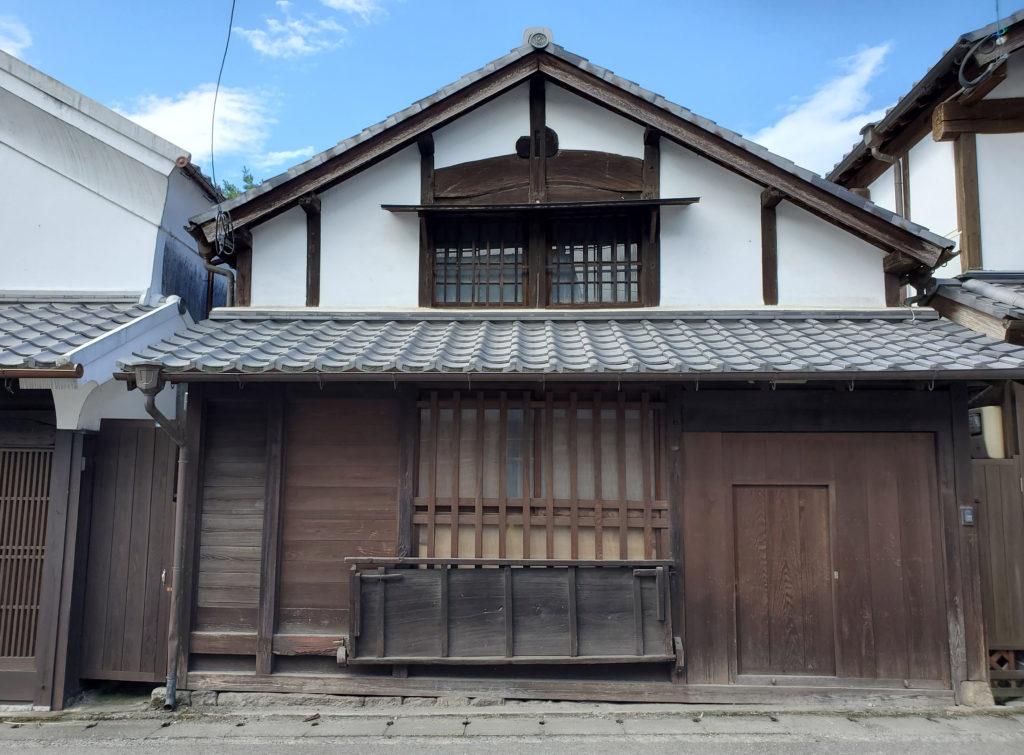 切妻屋根、漆喰壁、木の格子・板壁の家