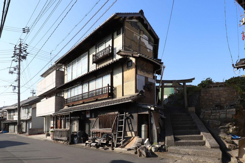 3階建ての元妓楼の裏に鳥居と階段が見える