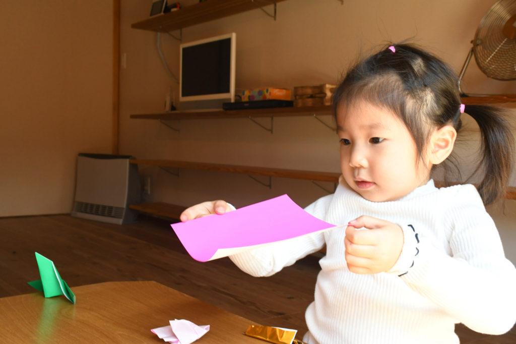 折り紙で遊ぶ子